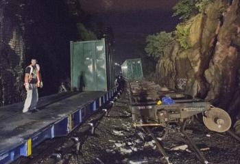 Worker Stands on FLatbed During Derailment Salvage Operations
