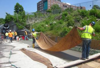 Workers laying wet burlap over new concrete on north end of the bridge